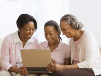 Three women of different generations smiling and looking together at a computer laptop screen