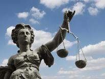 Legal Services for Seniors - statue of justice holding a scale, against a blue sky with clouds